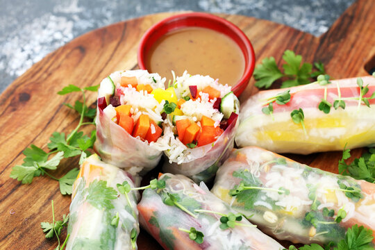 Fried chinese spring rolls with sweet chili sauce on rustic background