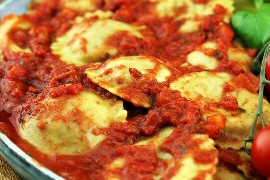 Ravioli with tomato sauce and basil on rustic background