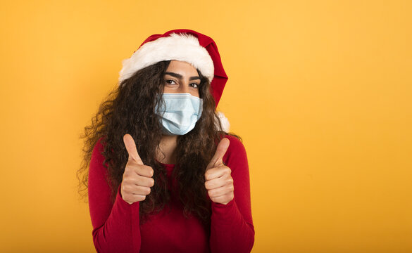 Woman with Christmas hat is optimistic about the defeat of covid 19 coronavirus. yellow background.