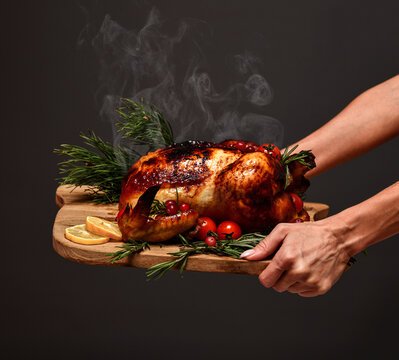 Woman hands hold plate with cooked thanksgiving turkey or chicken for christmas dinner evening with steam smoke on wooden rustic plate garnished with cherry berries and fruits on dark background