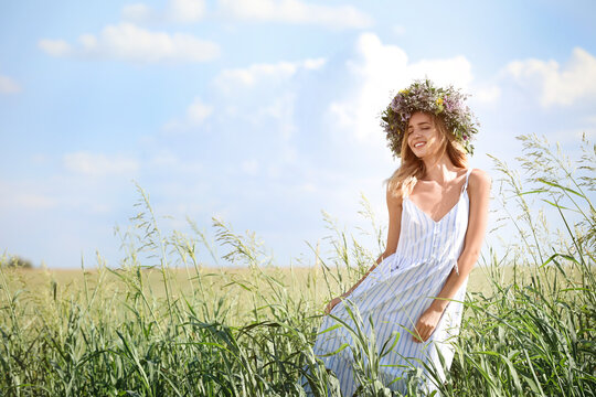 Young woman wearing wreath made of beautiful flowers in field on sunny day