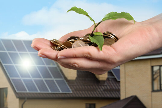 Woman holding coins and green sprout against house with installed solar panels on roof, closeup. Economic benefits of renewable energy