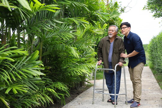 Happy elder Asian man using walker while walking for exercise around the garden with his son taking care of him at the retirement age with copy space