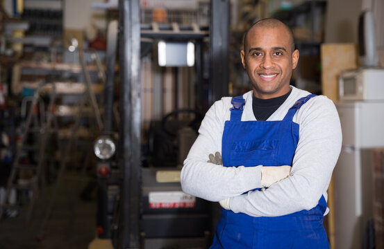 Skilled hispanic worker of building materials warehouse posing near racks with goods