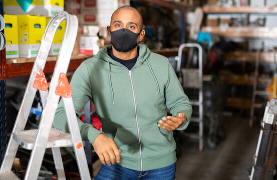 Portrait of confident Hispanic man owner of hardware store in protective face mask posing among shelving with goods. New lifestyle in concept of coronavirus pandemic