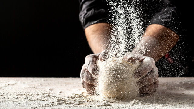 Hands of baker kneading dough isolated on black background. prepares ecologically natural pastries