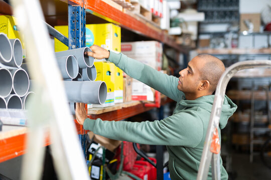 Focused Latino choosing supplies for home renovation in shop of building materials