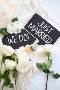 'Just Married' and 'We Do' banner with wedding rings on white flowers