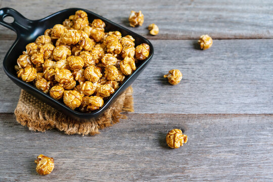 Flat lay of tasty caramel popcorn in black ceramic pan plate with sack table cloths on wooden table, close up.