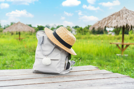 Backpack with straw hat and sunglasses on field. Travel concept.