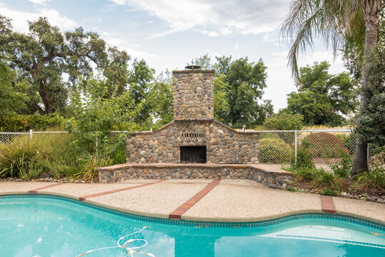 Northern California suburban villa backyard with pool and fireplace