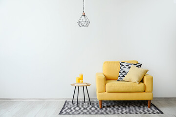 Stylish armchair with pillows and table with candles near light wall in room