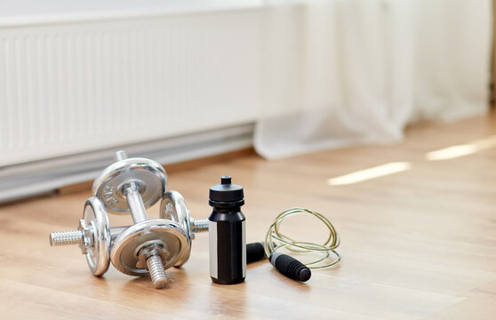 sport, fitness and objects concept - dumbbells, skipping rope and bottle on floor at home