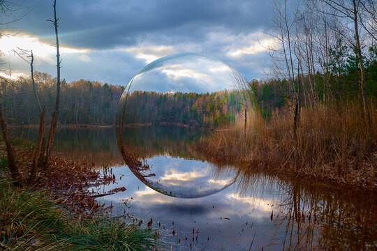 a glass ball hovers over a lake in an idyllic and beautiful landscape