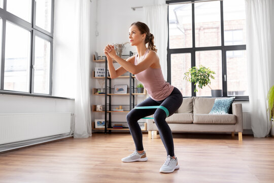 sport, fitness, lifestyle and people concept - woman exercising with resistance band at home