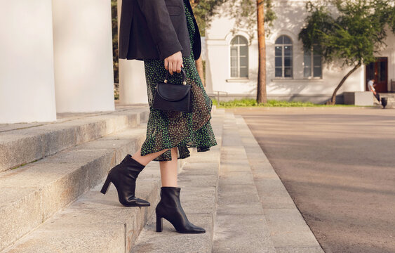 woman pose in black ankle boots on the stairs, street style outfit