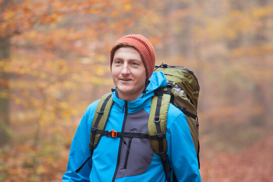 Young man hiking with backpack in a forest in fall