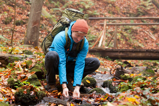 Backpacker scooping water from a mountain creek in autumn