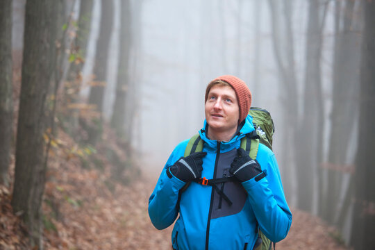 Young man hiking with backpack in a forest in winter