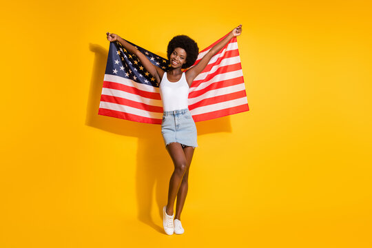Full length body size view of pretty slim cheerful wavy-haired girl holding us flag having fun isolated over shine yellow color background