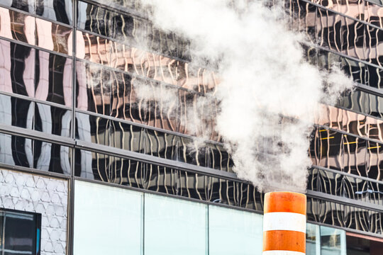 Close up picture of a steam pipe on the street of Manhattan with modern building in background, New York, USA.
