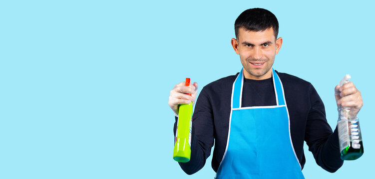 Banner-long format. Handsome man in rubber gloves and with spray guns in his hands posing and looking at the camera. Photo over white background with empty side space. Gender stereotypes concept