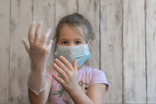 A little girl with a medical mask put on disposable gloves and admires how well she did, spoiling the coronavirus, in a pink t-shirt, can't put on a glove, wooden background photos