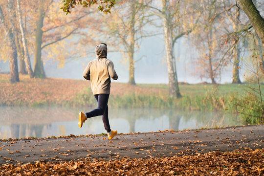 Autumn run in the park, male runner exercising at morning