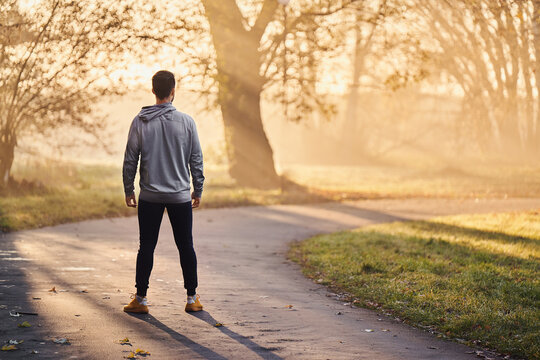 Athletic runner standing in park at autumn or winter morning