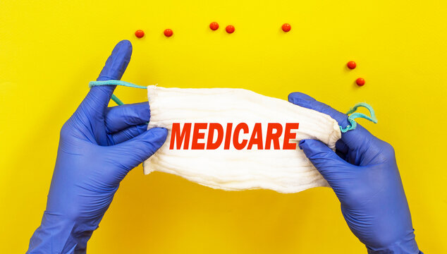 Doctor, woman holding a mask with the text MEDIGAP on a yellow background, near a pill. Medical concept.