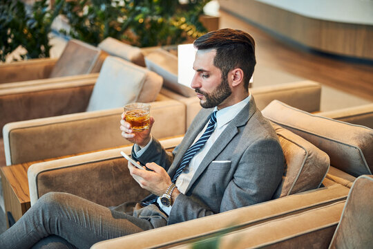 Business executive raising a whisky glass and using his cellphone