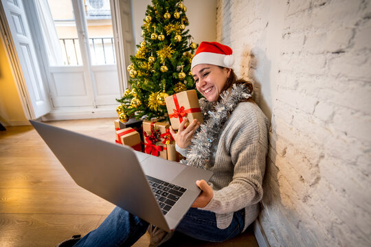 Happy woman on video call celebrating Virtual christmas with family online at home in lockdown