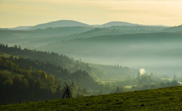 Spring morning rural landscape. The Carpathian Mountains in the morning through the fog