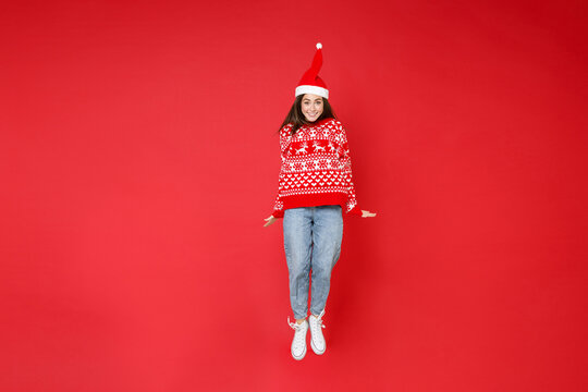 Full length of smiling young brunette Santa woman 20s wearing sweater, Christmas hat jumping having fun isolated on red background, studio portrait. Happy New Year celebration merry holiday concept.