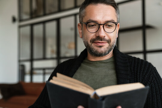 Confident young businessman reading book