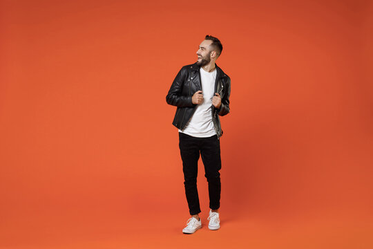 Full length of cheerful laughing funny excited young bearded man wearing basic white t-shirt black leather jacket standing looking aside isolated on bright orange colour background studio portrait.