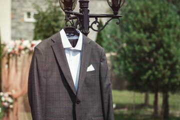 Close-up of man's brown checkered suit hanging on the street lamp Fotomurales