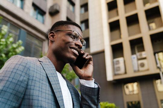 Joyful african american man talking on mobile phone while walking on street