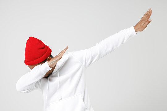 Young african american man 20s in basic casual streetwear hoodie doing dab hip hop dance hands gesture, youth sign hiding and covering face isolated on white colour wall background, studio portrait.