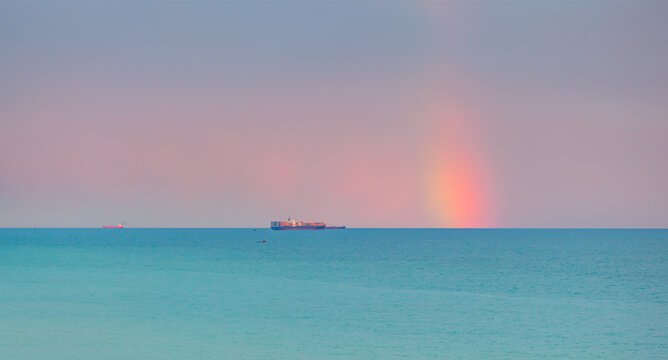 Container cargo ship with stormy sea and sky, amazing rainbow in the background