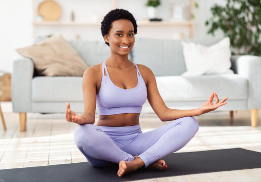 Smiling black woman in sportswear sitting on yoga mat in lotus pose and meditating or doing breathing exercises, indoors