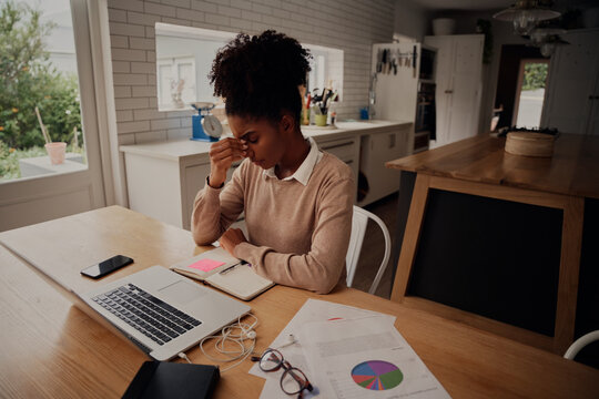 Young frustrated woman working at home in front of laptop suffering from headache