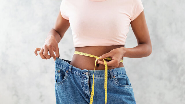 Black woman in old big jeans measuring her waist, showing results of slimming diet or liposuction, grey background