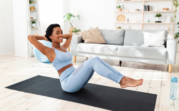 Full length portrait of young black woman exercising on sports mat, training her core muscles at home