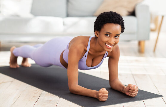 Full length portrait of smiling black woman in sportswear doing elbow plank on sports mat at home