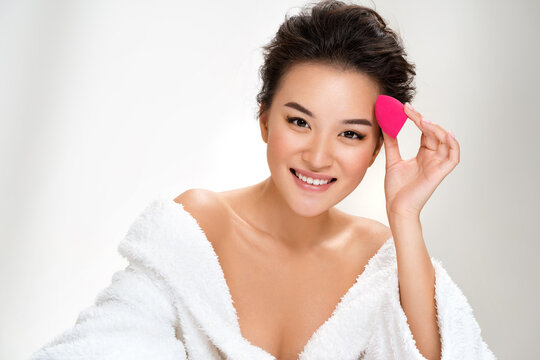 Woman applying foundation using cosmetic sponge, beauty blender. Photo of asian woman after shower on white background. Beauty and skin care concept