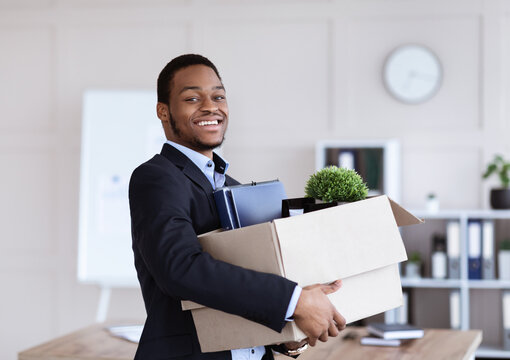Happy black businessman moving office with box and his belongings