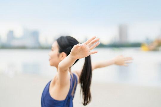 都市のビーチでストレッチと深呼吸をする若い女性