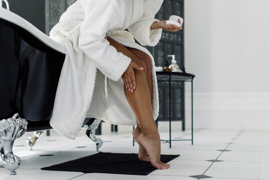 Afro american woman in bathrobe spending morning in bathroom