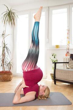Pregnant woman practicing yoga doing Viparita Karani position